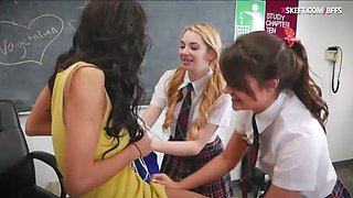 Schoolgirls make out with their classmate in the classroom