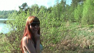 Lean pale skin redhead girl flashes her pussy by the lake