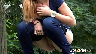 Sporty blonde sweetie sits on the tree stub and pees