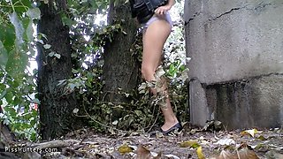 Woman ###ing in the bushes of a city park