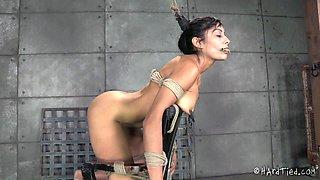 Alluring slaved brunette in bondage being worked on using sex machine in BDSM shoot