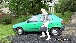 Bright blondie in white pants sits near the green car and pisses